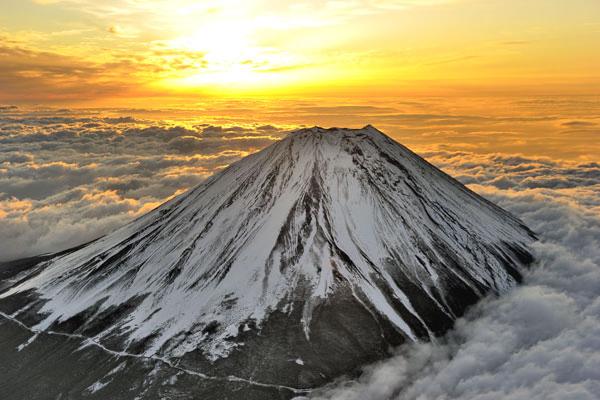 朝日に染まる雲海に立つ富士山