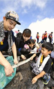 登山道を歩きながらごみを拾う参加者=富士山6合目