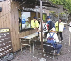 今夏から設置された徴収所で富士山保全協力金を支払う登山者ら=富士山6合目