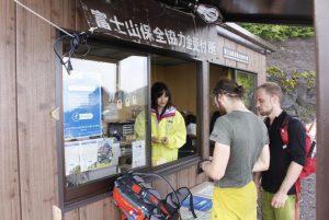 今夏から設置した徴収所で富士山保全協力金を支払う登山者ら=富士山6合目(8月1日)