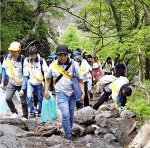 緑のごみ袋を持って登山道のごみを集める参加者=富士山6合目付近