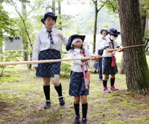 目隠しをして森林を歩く隊員ら=富士吉田市青少年センター