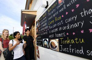 外国人観光客に英語の看板を示して和食の案内をする林理恵子さん(右)=富士吉田市新町2丁目