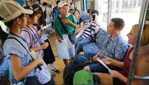 外国人観光客に大月の観光地を英語で紹介する児童と生徒=富士急行線大月駅