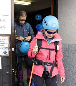 借りたヘルメットを着用して登山に向かう人たち=富士山6合目の安全指導センター