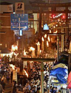 たいまつの炎が照らす通りを多くの人が行き交う。右奥は金鳥居