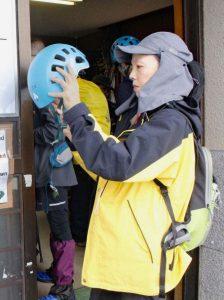 借りたヘルメットを着用する登山者=富士山6合目(8月30日撮影)