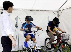 VRゴーグルを装着して東京五輪自転車ロードレースのコースを体感する子どもら=山中湖村平野