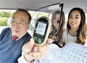 多言語翻訳機を使って外国人の乗客に観光案内をしているタクシー運転手の小野田忠男さん(左)=富士河口湖町内