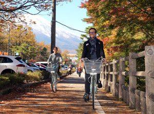 自転車で村内を散策するブランドン・プレッサーさん(右)とマヤ・カチュール・レヴィンさん(左)=山中湖村平野