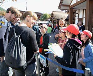 外国人観光客にインタビューする児童=富士急行線河口湖駅