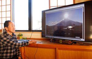 撮影した富士山の画像を確認する大田黒敦雄さん=忍野村内野