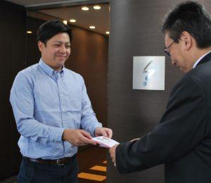 目録を手渡すマリーナベイ・シッピング社セールス・アシスタントの安藤亮一さん(左)=甲府・山日YBS本社