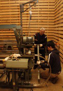 企画展で展示する織り機を準備する渡辺徳重さん(奥)ら=富士吉田市富士見1丁目