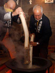 釜に「粥柱」を入れ、かゆを煮る占人=富士吉田・小室浅間神社