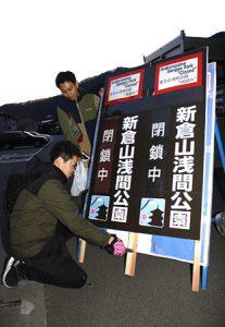 新倉山浅間公園が閉鎖していることを知らせる看板を設置する富士吉田市職員=富士吉田市浅間2丁目