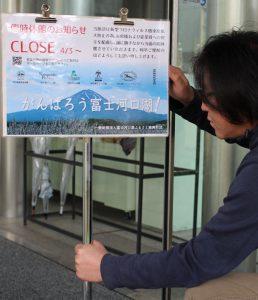 臨時休館を知らせる案内を設置する富士河口湖ふるさと振興財団のスタッフ=富士河口湖町河口