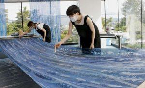 カーテン作りの作業を公開した坂本美紗希さん(右)=富士吉田市立図書館
