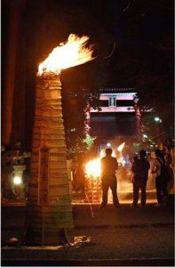 参道を照らすたいまつの炎。右奥は大鳥居=富士吉田・北口本宮冨士浅間神社