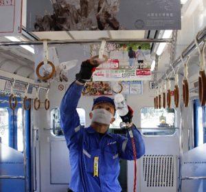 つり革の抗菌作業をする社員=富士河口湖・富士急行線河口湖駅