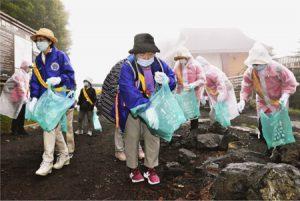 マスクを着け、ごみを拾い集める参加者=富士山5合目