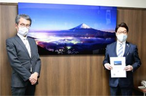 新道峠から撮影した写真を笛吹市に寄贈したTAKASHIさん(左)=笛吹市役所