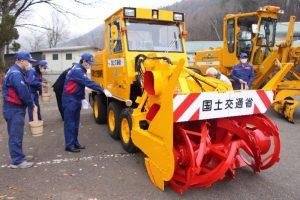 富士山の湧き水で除雪車を清める浜谷健太所長ら=鳴沢村総合センター