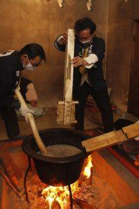釜に入ったかゆをかき混ぜる占人=富士吉田・小室浅間神社