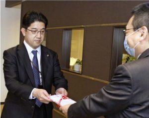 担当者に目録を手渡す松本卓士所長(左)=甲府・山日YBS本社
