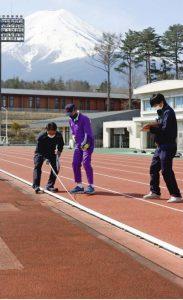 富士北麓公園陸上競技場について、第2種競技場としての規格を満たすかどうか検定する日本陸連の担当者ら=富士吉田市内(3月27日)