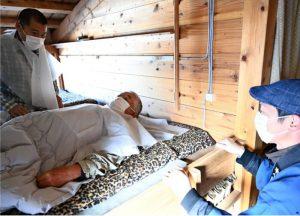 個室化した就寝スペースで宿泊者に不織布シートの付け方を説明する従業員(右)=富士山・本八合目トモエ館