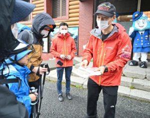 安全登山に関するパンフレットを手渡して登山上の注意を呼び掛ける署員(右)=富士山5合目