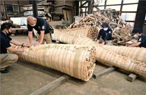 26、27日の吉田の火祭りで使用するために、完成したたいまつを確認する世話人ら=富士吉田木材流通センター